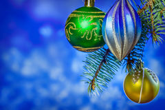 Christmas card. three Christmas decorations on the tree on blue blurred background. Christmas card. three Christmas ornaments green, blue, yellow on a tree on a Royalty Free Stock Image