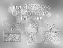 Christmas card. Three hand - drawn Christmas gifts and Christmas lettering on silver bokeh background with lights Stock Images