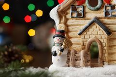 Christmas card with toy fairy house with snowman and garland bokeh. Royalty Free Stock Photo