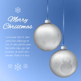 Christmas card with two silver pendants in the shape of a ball. Decorated with snowflakes and snowman. Classic blue background wit. H place for your text. Vector Stock Photos