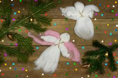 Christmas card: two white woolen angels flying, colorful confetti and branches on wood plank. Royalty Free Stock Photos