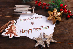 Christmas card with various decorations and greetings on wooden. Christmas card with various decorations and white paper with greetings text on wooden background Royalty Free Stock Image