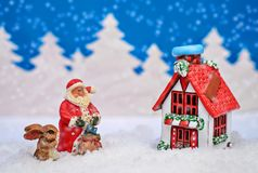 Christmas card with red house, Santa and Bunny and it`s snowing. Christmas card where Santa and the Bunny are outside the house with a red roof next to a fir Royalty Free Stock Images