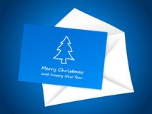 Christmas card on white envelope. Blue christmas card with white envelope on blue background Royalty Free Stock Photo
