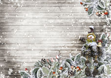 Christmas card on a wooden board with beautiful snowy leaves
