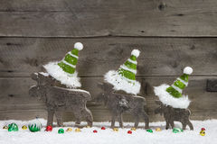 Christmas card with wooden elk or reindeer green white - decoration. Funny christmas card with three elks wearing green santa hats for a greetings on a grey Royalty Free Stock Photos