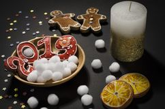 Christmas card: on a wooden plate are red ginger cookies in the shape of numbers 2019 and white round snowflakes. Christmas card: on a wooden plate there are red royalty free stock images