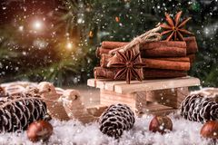 Christmas card with wooden sled with heap of cinnamon. Over old wooden background with falling snow Stock Photography