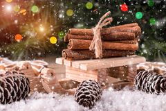 Christmas card with wooden sled with heap of cinnamon. Over old wooden background with falling snow Royalty Free Stock Photo