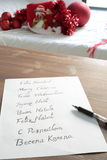 Christmas card written in several languages. Christmas greeting in several languages written on white paper on a wooden table Stock Photos