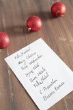 Christmas card written in several languages. Christmas greeting in several languages written on white paper on a wooden table Royalty Free Stock Images