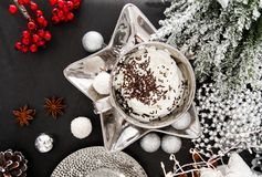 Christmas card silver cup of sweet whipped cream on black table, with sweets, cinnamon, aniseed, winter cone, and glass royalty free stock photo
