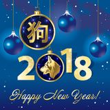 Christmas card for the year 2018 with a gold dog. And blue Christmas balls on blue background Stock Photo