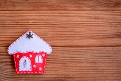 Merry Christmas card. Winter holiday background. Christmas felt house decoration isolated on a brown wooden background Stock Photos