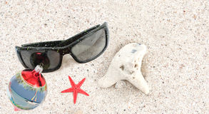 Christmas in Caribbean. An angle closeup view of a pair of sunglasses, christmas bulb, red star fish, coral and sea shell on some white beach Caribbean sand Royalty Free Stock Images