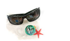 Christmas at a Caribbean Resort. An isolated angled closeup view of a pair of sunglasses, christmas bulb, red star fish, on some white sand. Pool reflections in Royalty Free Stock Photo