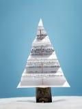 Christmas carol tree. Paper christmas tree with christmas carol notes over light blue background Stock Photo