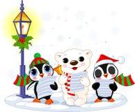 Christmas caroler. S � cute polar bear and two penguins- under streetlight Stock Photos