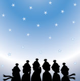Christmas Carolers. Silhouette of Christmas carolers on snowy gradient background Stock Photos