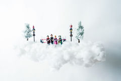 Christmas carolers floating on a cloud of cotton. Conceptual levitation Stock Photo
