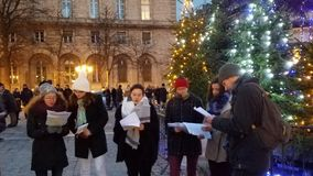 Christmas Carolers at Notre Dame Cathedral. Christmas carolers gather at the Christmas tree in front of Notre Dame Cathedral in Paris, France Royalty Free Stock Photography