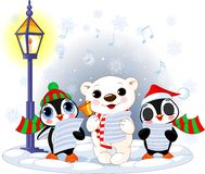 Christmas carolers. Polar bear and two penguins. Christmas carolers. Cute polar bear and two penguins- under streetlight Royalty Free Stock Images