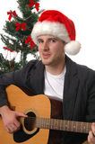 Christmas Carols. A young man in a Santa hat playing the guitar and singing Christmas Carols royalty free stock image