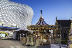 Vintage Christmas Carousel with Modern Building in Background. Christmas Carousel in Birmingham City against Bullring Building royalty free stock photo