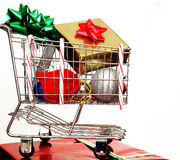 Christmas Cart. A shopping cart with Christmas items, sitting on top of a present Royalty Free Stock Photo