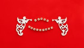 Christmas carved wooden angels with trumpet and words Merry Christmas on little bricks on red background royalty free stock photography