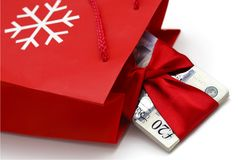 Christmas cash prize. Stack of twenty British Pounds Sterling tied up with red shiny ribbon falling out a red Christmas gift bad on white background Royalty Free Stock Photography