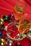 Christmas celebration. Champagne glasses surrounded by christmas ornaments, on red Stock Photography