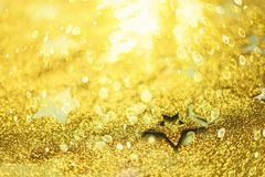 Christmas celebration. Abstract background for new year party. Patter of gold stars with lights, bokeh. Golden glitter stars on. Yellow shimmer texture royalty free stock images