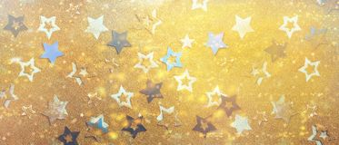 Christmas celebration. Abstract background for new year party. Patter of gold stars with lights, bokeh. Golden glitter stars on. Yellow shimmer texture stock photography