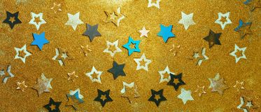 Christmas celebration. Abstract background for new year party. Patter of gold stars with lights, bokeh. Golden glitter stars on. Yellow shimmer texture. Banner royalty free stock photography