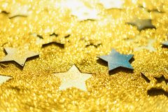 Christmas celebration. Abstract background for new year party. Patter of gold stars with lights, bokeh. Golden glitter stars on. Yellow shimmer texture stock photos