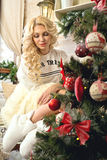 Christmas Celebration. Blonde girl sitting on a bench near a Christmas tree decorated with toys. Volgograd. Volgograd region. November 8, 2015 Stock Photo