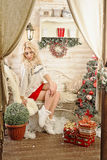 Christmas Celebration. Celebration. Blonde girl sitting on a bench near a  tree decorated with toys. Volgograd. Volgograd region. November 8, 2015 Royalty Free Stock Photos