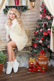 Christmas Celebration. Blonde girl sitting on a bench near a Christmas tree decorated with toys, wrapped in a warm blanket. Volgograd. Volgograd region Royalty Free Stock Image