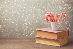 Christmas celebration with candy cane and cup on books over bokeh background Royalty Free Stock Photography
