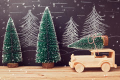 Christmas celebration concept with Christmas tree on toy car on wooden table over chalkboard background Royalty Free Stock Photos
