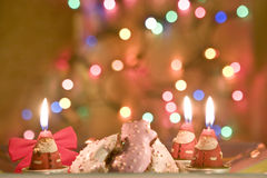 Christmas celebration cookies and Santa candles. Christmas cookies and Santa Claus candles with colored lights Royalty Free Stock Images
