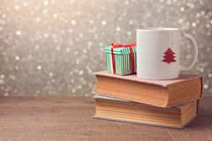 Christmas celebration with cup and gift box on books over bokeh background Stock Image