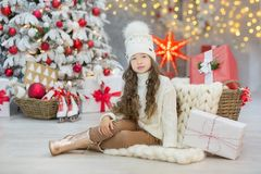 Christmas celebration. Cute little girl in a beautiful dress sitting near the Christmas tree. Christmas miracles. Luxurious Christ Stock Images
