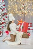 Christmas celebration. Cute little girl in a beautiful dress sitting near the Christmas tree. Christmas miracles. Luxurious Christ Stock Image