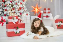 Christmas celebration. Cute little girl in a beautiful dress sitting near the Christmas tree. Christmas miracles. Luxurious Christ Royalty Free Stock Images