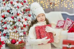Christmas celebration. Cute little girl in a beautiful dress sitting near the Christmas tree. Christmas miracles. Luxurious Christ Royalty Free Stock Photo