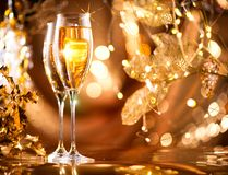 Christmas celebration. Flutes with sparkling champagne. Over holiday glowing background Stock Image