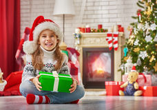 Christmas celebration. Funny smiling child in Santa red hat holding Christmas gift in hand stock image
