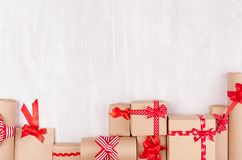Christmas celebration gifts with red ribbons and bows on white wood bacground, copy space, top view stock image